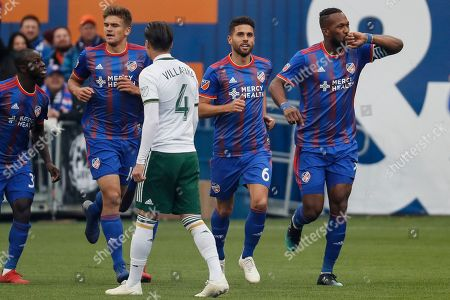 FC Cincinnati defender Kendall Waston, right, celebrates after scoring in the first half of an MLS soccer match against the Portland Timbers, in Cincinnati