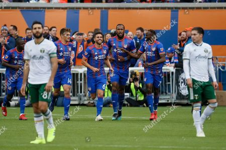 FC Cincinnati defender Kendall Waston, center right, celebrates after scoring in the first half of an MLS soccer match against the Portland Timbers, in Cincinnati