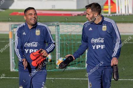 Argentina's national soccer player Gabriel Mercado, left, and teammate German Pezzella arrive at a training session in Madrid, Spain, . Argentina will play a friendly soccer match against Venezuela on Friday