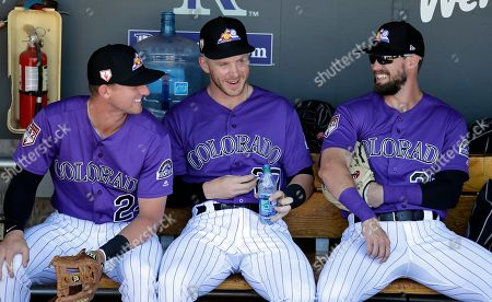Colorado Rockies' Ryan McMahon, left, Trevor Story and David Dahl wait to head onto the field before a spring training baseball game against the Cincinnati Reds, in Scottsdale, Ariz