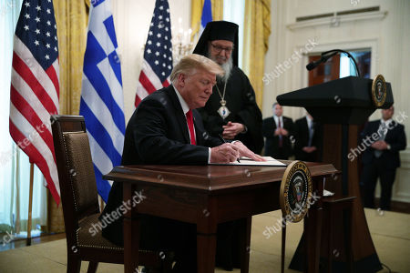 US President Donald J. Trump signs a proclamation as Archbishop Demetrios (R), Geron of America, looks on in a Greek Independence Day celebration at the East Room of the White House in Washington, DC, USA, 18 March 2019.