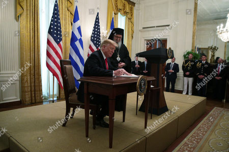 US President Donald J. Trump signs a proclamation as Archbishop Demetrios (R), Geron of America, looks on during a Greek Independence Day celebration at the East Room of the White House in Washington, DC, USA, 18 March 2019.