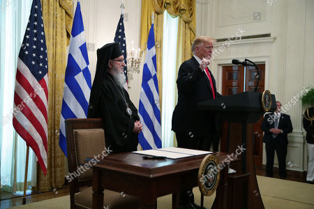 US President Donald J. Trump speaks as Archbishop Demetrios, Geron of America, listens during a Greek Independence Day celebration in the East Room of the White House in Washington, DC, USA, 18 March 2019.
