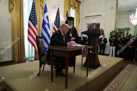 United States President Donald J. Trump signing a proclamation as Archbishop Demetrios of America (R), Geron of America, looks on during a Greek Independence Day celebration at the East Room of the White House.