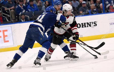 Tampa Bay Lightning defensemen Erik Cernak (81) and Ryan McDonagh (27) stop Arizona Coyotes center Clayton Keller (9) during the third period of an NHL hockey game, in Tampa, Fla