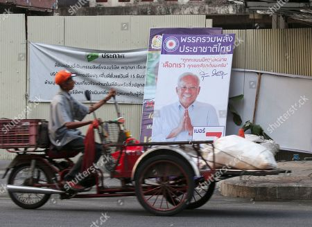A Thai man rides a vehicle for collecting recyclable garbage past an election campaign poster of Suthep Thaugsuban (R), Thai former protest leader of People's Democratic Reform Committee and former of Democrat Party secretary-general, along a road ahead of the upcoming general election in Bangkok, Thailand, 19 March 2019. Thailand has more than one hundred political parties registered for the upcoming general election to be held on 24 March 2019, the first poll in five years since the May 2014 military coup.