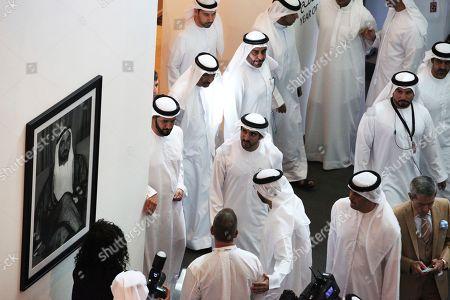 Stock Photo of Dubai's crown prince, Sheikh Hamdan bin Mohammed Al Maktoum, center, looks at a picture of the late ruler of Abu Dhabi Sheikh Zayed bin Sultan Al Nahyan at Art Dubai in Dubai, United Arab Emirates, . Art Dubai is marking its 13th edition with an exhibition running March 20 through March 23