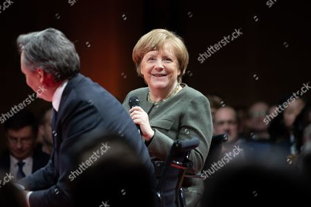 German Chancellor Angela Merkel (R) speaks next to Bloomberg editor-in-chief John Micklethwait (L) during the Global Solutions Summit in Berlin, Germany, 19 March 2019. Representatives from politics, business and society meet in the German capital.