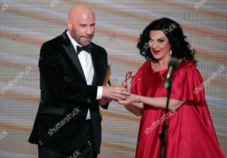 Romanian soprano Angela Gheorghiu (R) receives a trophy from US actor John Travolta (L) during the 2nd award ceremony of the International Professional Music Award 'BraVo' in the field of classical arts at the Bolshoi Theatre in Moscow, Russia, 19 March 2019.