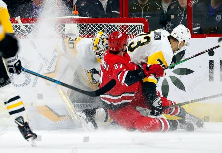 Carolina Hurricanes' Andrei Svechnikov (37) and Pittsburgh Penguins' Jack Johnson (73) collide with goaltender Matt Murray (30) during the second period of an NHL hockey game, in Raleigh, N.C