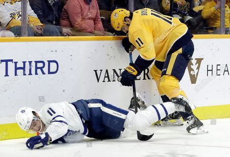 Nashville Predators center Brian Boyle, right, checks Toronto Maple Leafs left wing Zach Hyman, left, off the puck in the first period of an NHL hockey game, in Nashville, Tenn