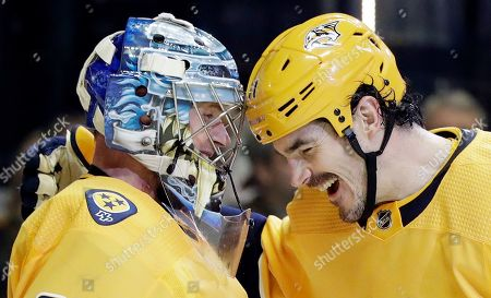 Nashville Predators goaltender Pekka Rinne, of Finland, left, is congratulated by center Brian Boyle after Rinne shut out the Toronto Maple Leafs 3-0 in an NHL hockey game, in Nashville, Tenn