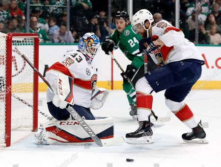 Florida Panthers goaltender Sam Montembeault (33) and defenseman Aaron Ekblad, right, defend against a shot as Dallas Stars left wing Roope Hintz (24) watches in the first period of an NHL hockey game in Dallas