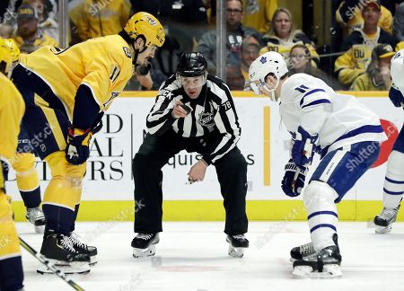 Linesman Brian Mach (78) prepares to drop the puck for Nashville Predators center Brian Boyle, left, and Toronto Maple Leafs left wing Zach Hyman, right, in the first period of an NHL hockey game, in Nashville, Tenn