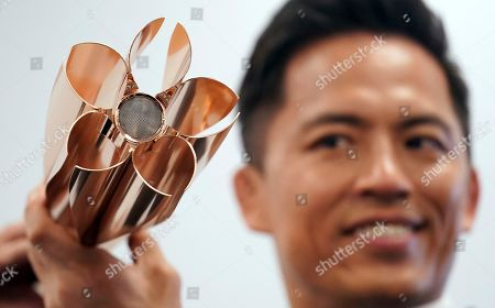 Former judo Olympic medalist Tadahiro Nomura holds the Olympic torch of the Tokyo 2020 Olympic Games during a press conference in Tokyo . The Tokyo Olympics open on July 24, 2020