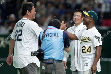 Former Oakland Athletics and Baseball Hall of Fame player Rickey Henderson (R) shakes hands with former Seattle Mariners player Kazuhiro Sasaki (L) while former Seattle Mariners player Kenji Jojima (2-R) looks on after the ceremonial first pitch prior to the start of the the first game between the Oakland Athletics and the Seattle Mariners during the Major League Baseball (MLB) Opening Games at Tokyo Dome in Tokyo, Japan, 20 March 2019.