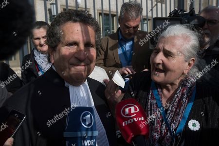 Munira Subasic of the Mothers of Srebrenica, right, offers a handkerchief as she haggles Peter Robinson of the U.S., lawyer for former Bosnian Serb leader Radovan Karadzic, left, after the court upheld Karadzic's conviction at International Residual Mechanism for Criminal Tribunals in The Hague, Netherlands, . Nearly a quarter of a century since Bosnia's devastating war ended, Karadzic heard the final judgment upholding 2016 convictions for genocide, crimes against humanity and war crimes, and an increase from his 40-year sentence to life