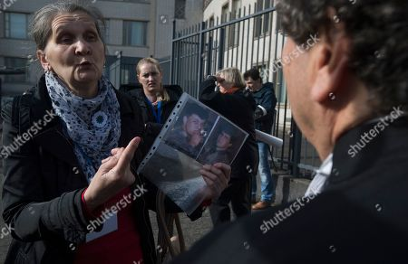 A woman with the Mothers of Srebrenica, holds the photographs of two victims of the Bosnian war as she talks to Peter Robinson of the U.S., lawyer for former Bosnian Serb leader Radovan Karadzic, right, after the court upheld Karadzic's conviction at International Residual Mechanism for Criminal Tribunals in The Hague, Netherlands, . Nearly a quarter of a century since Bosnia's devastating war ended, Karadzic heard the final judgment upholding 2016 convictions for genocide, crimes against humanity and war crimes, and an increase from his 40-year sentence to life