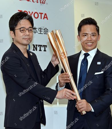 Tadahiro Nomura, three-time Olympic judo champion, shows the Olympic torch