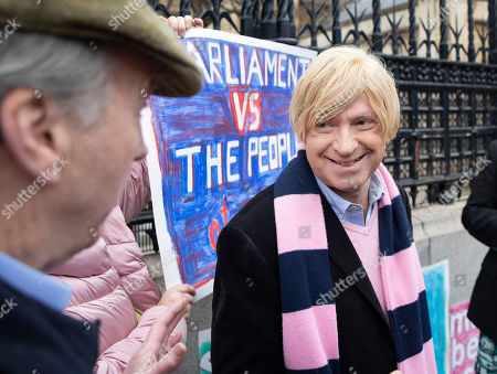 Michael Fabricant MP stands amongst demonstrators as he arrives at Parliament.