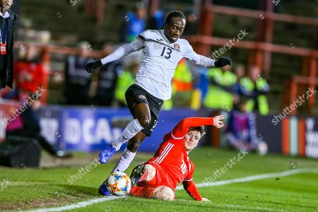 Stock Picture of Wales midfielder Lee Evans slides in and tackles Trinidad and Tobago midfielder Nathan Lewis during the Friendly European Championship warm up match between Wales and Trinidad and Tobago at the Racecourse Ground, Wrexham