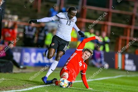 Stock Photo of Wales midfielder Lee Evans slides in and tackles Trinidad and Tobago midfielder Nathan Lewis during the Friendly European Championship warm up match between Wales and Trinidad and Tobago at the Racecourse Ground, Wrexham
