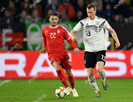Germany's Lukas Klostermann, right, and Serbia's Adem Ljajic run for the ball during a international friendly soccer match between Germany and Serbia at the Volkswagen Arena stadium in Wolfsburg, Germany