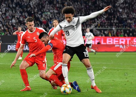 Germany's Leroy Sane, right, duels for the ball with Serbia's Antonio Rukavina, center, and Serbia's Uros Spajic during a international friendly soccer match between Germany and Serbia at the Volkswagen Arena stadium in Wolfsburg, Germany