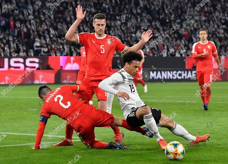 Germany's Leroy Sane, right, duels for the ball with Serbia's Antonio Rukavina, left, and Serbia's Uros Spajic during a international friendly soccer match between Germany and Serbia at the Volkswagen Arena stadium in Wolfsburg, Germany