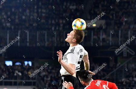 Germany's Marcel Halstenberg, top, jumps for the ball with Serbia's Antonio Rukavina during a international friendly soccer match between Germany and Serbia at the Volkswagen Arena stadium in Wolfsburg, Germany