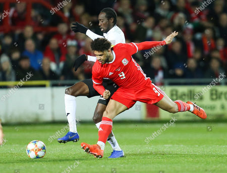 Nathan Lewis of Trinidad and Tobago and Tyler Roberts of Wales compete for the ball
