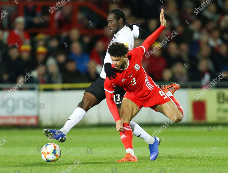 Stock Image of Nathan Lewis of Trinidad and Tobago and Tyler Roberts of Wales compete for the ball