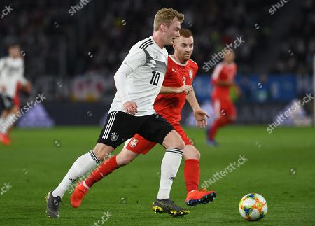 Germany´s Julian Brandt (L)  in action against Serbia´s Milos Bogosavac (R) during the international friendly soccer match between Germany and Serbia in Wolfsburg, Germany, 20 March 2019.