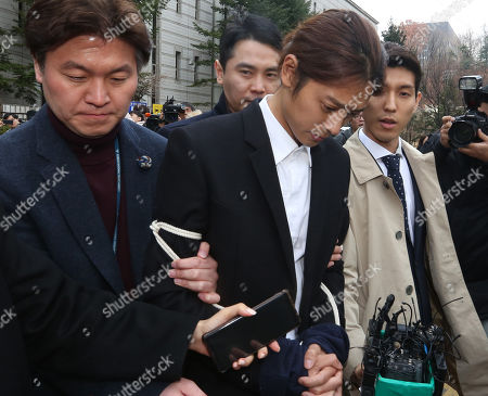 Stock Picture of South Korean K-pop star Jung Joon-young (C), walks with policemen (R and L) while waiting of the court's decision at the Seoul District Court in Seoul, South Korea, 21 March 2019. The popstar was at court to attend a hearing after he admitted to secretly filming himself engaging in sexual activities with ten or more women and sharing the footage.