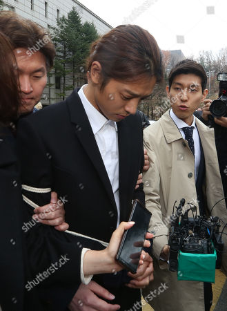 South Korean K-pop star Jung Joon-young (C), walks with policemen while waiting of the court's decision at the Seoul District Court in Seoul, South Korea, 21 March 2019. The popstar was at court to attend a hearing after he admitted to secretly filming himself engaging in sexual activities with ten or more women and sharing the footage.