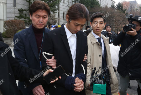 South Korean K-pop star Jung Joon-young (C), walks with policemen (R and L) while waiting of the court's decision at the Seoul District Court in Seoul, South Korea, 21 March 2019. The popstar was at court to attend a hearing after he admitted to secretly filming himself engaging in sexual activities with ten or more women and sharing the footage.