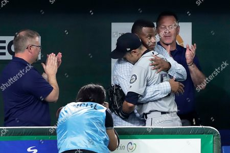 Outfielder Ichiro Suzuki of the Seattle Mariners embraces former Seattle Mariners and Baseball Hall of Fame player George Kenneth 'Ken' Griffey Jr. as he leaves for replacement in the eighth inning of the second game between the Oakland Athletics and the Seattle Mariners during the Major League Baseball (MLB) Opening Games at Tokyo Dome in Tokyo, Japan, 21 March 2019.