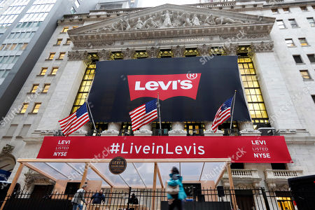 A Levi's banner adorns the facade of the New York Stock Exchange, . Levi Strauss & Co., which gave America its first pair of blue jeans, is going public for the second time. The 166-year-old company, which owns the Dockers and Denizen brands, previously went public in 1971, but the namesake founder's descendants took it private again in 1985