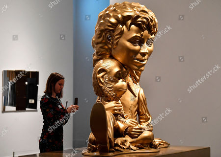 A visitor takes a smartphone picture of the sculpture 'Michael Jackson and Bubbles' from US artist Paul McCarthy' at a preview of the exhibition 'Michael Jackson: On The Wall' at the Bundeskunsthalle museum in Bonn, Germany, . The exhibition around the controversial iconic pop idol is open until July 14