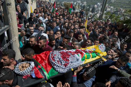 Stock Photo of Palestinian mourners carry the body of Ahmad Jamal Manasra, 26, during his funeral in the West Bank village of Wad Fokin, near Bethlehem, . The governor of the West Bank city of Bethlehem said Thursday that Israeli soldiers shot and killed an unarmed Palestinian man who was trying to aid another near the city