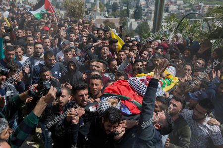Palestinian mourners carry the body of Ahmad Jamal Manasra, 26, during his funeral in the West Bank village of Wad Fokin, near Bethlehem, . The governor of the West Bank city of Bethlehem said Thursday that Israeli soldiers shot and killed an unarmed Palestinian man who was trying to aid another near the city