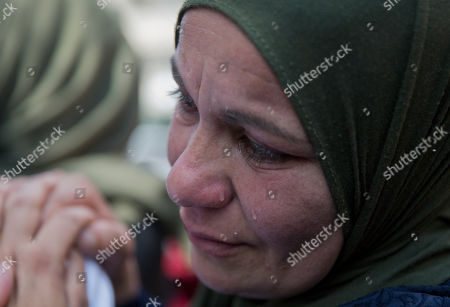 A mourning relative of Palestinian Ahmad Jamal Manasra, 26, cries during his funeral in the West Bank village of Wad Fokin, near Bethlehem, . The governor of the West Bank city of Bethlehem said Thursday that Israeli soldiers shot and killed an unarmed Palestinian man who was trying to aid another near the city