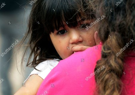 Stock Picture of Hillary Herrera Cortez, Hildy Cortez Martinez. Hillary Herrera Cortez, 3, peers over the shoulder of her mother, Hildy Cortez Martinez, as the two wait for Border Patrol agents to process them at the U.S.-Mexico border near McAllen, Texas. Hildy Cortez said she named her daughter after former U.S. Sen. Hillary Clinton