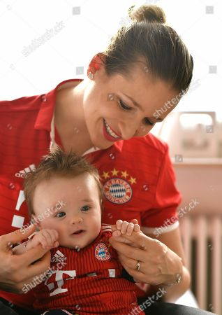 MODEL RELEASED Mother with baby, 3 months, in jersey of FC Bayern Munich, Baden-Wuerttemberg, Germany