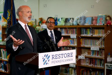 Tom Wolf, Nelson R. Reyes. Pennsylvania Gov. Tom Wolf, left, speaks as John H. Taggart School Principal Nelson R. Reyes looks on during a news conference at the school's library, in Philadelphia. Wolf discussed his infrastructure package, Restore Pennsylvania, to help remediate contaminants from Pennsylvania schools