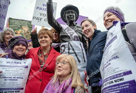 Stock Image of Nicola Sturgeon and Mhairi Black and a group of protesters seen posing for the media at the feet of the statue of Mary Barbour during the demonstration.