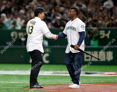 Former Oakland Athletics pitcher Keiichi Yabu, left, and former Seattle Mariners outfielder Ken Griffey Jr. shake hands after the ceremonial first pitch before Game 2 of the Major League baseball opening series between the Mariners and the Athletics at Tokyo Dome in Tokyo