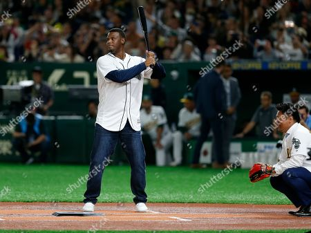 Former Seattle Mariners outfielder Ken Griffey Jr., left, and former Oakland Athletics third baseman Akinori Iwamura attend the ceremonial first pitch before Game 2 of the Major League baseball opening series between the Mariners and the Athletics at Tokyo Dome in Tokyo