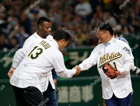 Former Oakland Athletics pitcher Keiichi Yabu (13) shakes hands with former Athletics third baseman Akinori Iwamura after attending the ceremonial first pitch along with former Seattle Mariners outfielder Ken Griffey Jr., back, before Game 2 of the Major League baseball opening series between the Mariners and the Athletics at Tokyo Dome in Tokyo
