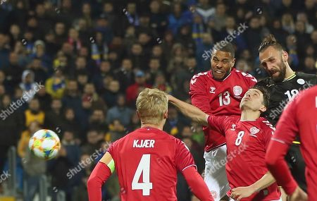 Kosovo's Vedat Muriqi, right, jumps for the ball with Denmark's Mathias Jorgensen, top left, during a international friendly soccer match between Kosovo and Denmark at Fadil Vokrri stadium in Pristina, Kosovo